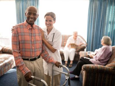 elder man using a walker with caregiver beside him
