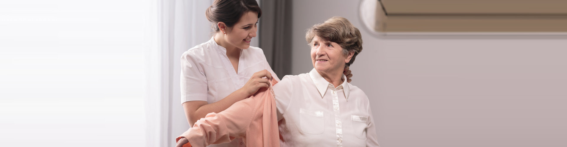 caregiver assisting elder woman on wearing a polo shirt concept