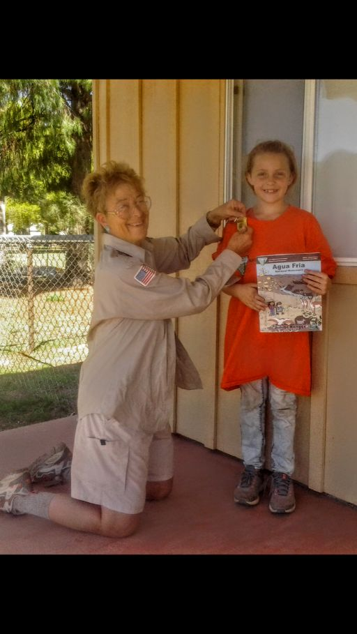 Marie Davis (BLM) awards a volunteer with a Junior Ranger Badge after tcompleting the Junior Ranger Book. he