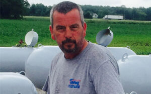picture of Terry, propane delivery driver, standing next to propane tanks