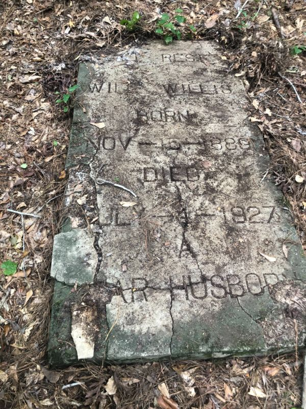 Cracked slab marker with engraved names and dates