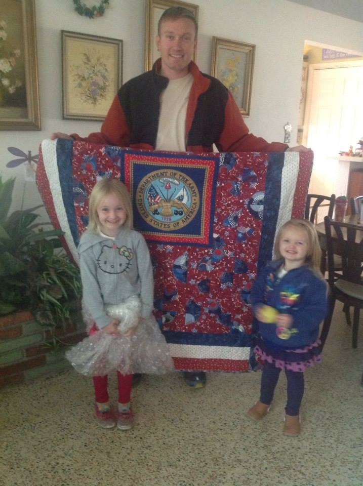 Troy Osten with his beautiful children and his Quilt of Valor
