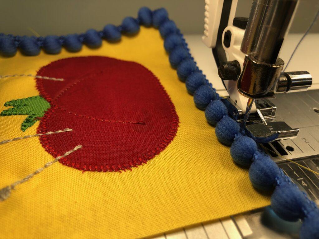 stitch pom-pom trim to sewing ornament