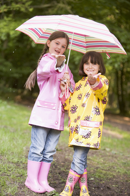 Two sisters outdoors in rain with umbrella smiling
