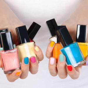 woman hand holding colorful nail-polish