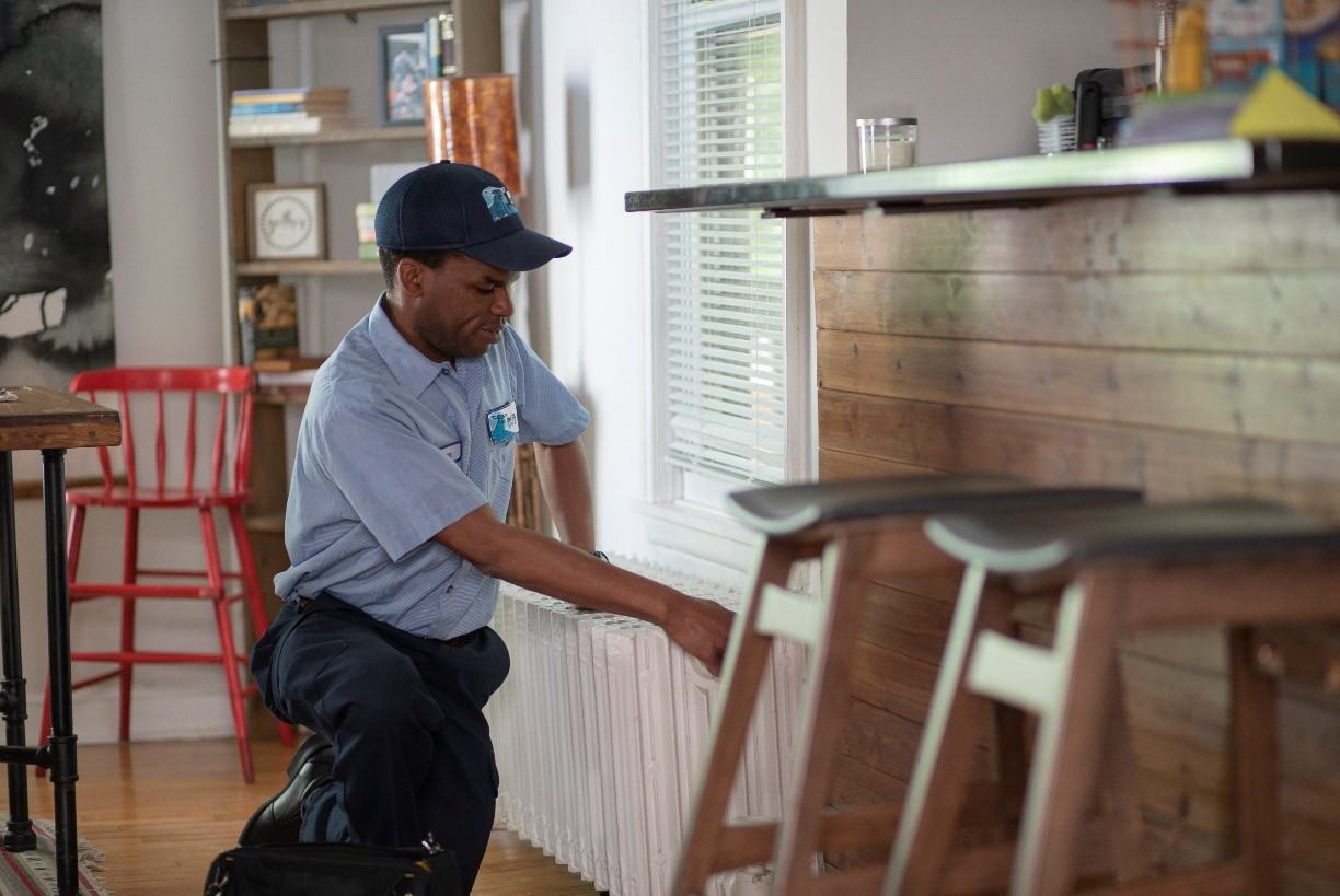 HVAC technician in home with blue hat