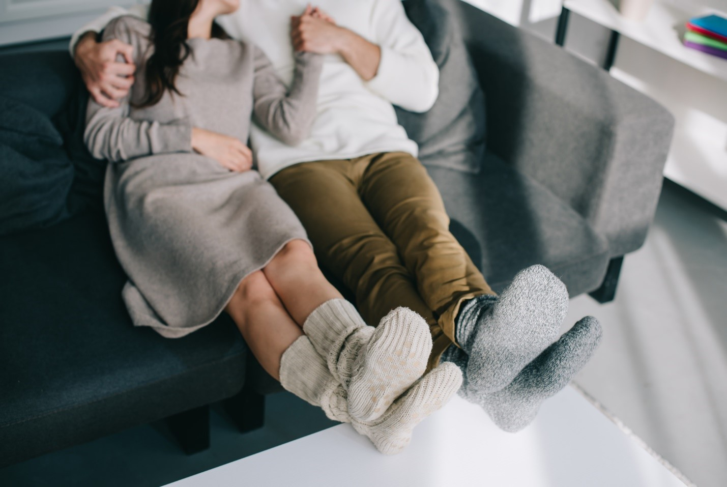 Two people on couch with socks on feet