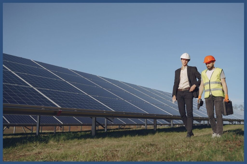 Man in a blazer and man wearing work vest walking past solar panels