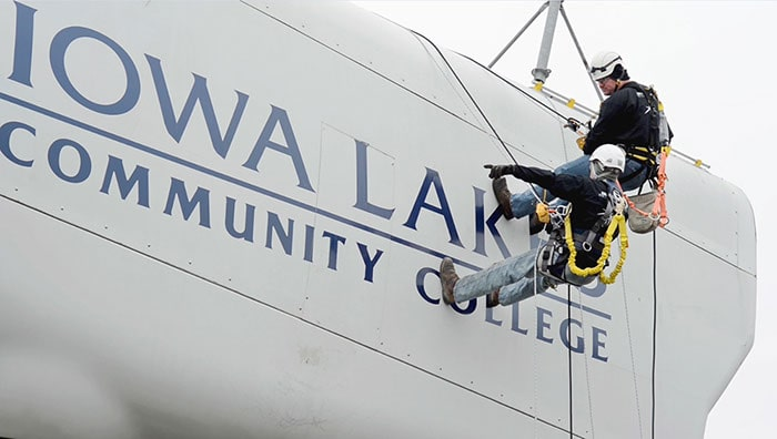 Two students on the side of wind energy equipment at Iowa Lakes Community College