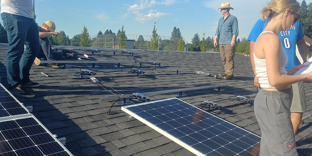 Close up of students installing solar panels at Clackamas Community College