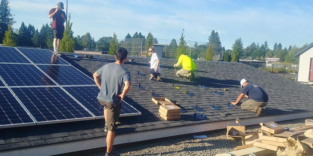 Students on demo roof installing solar panels at Clackamas Community College