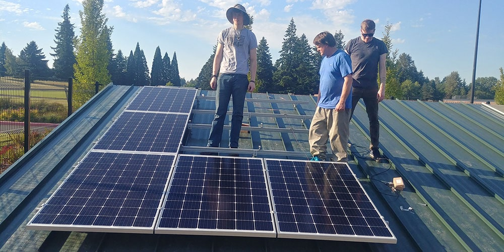 Students standing next to partially installed solar panels at Clackamas Community College