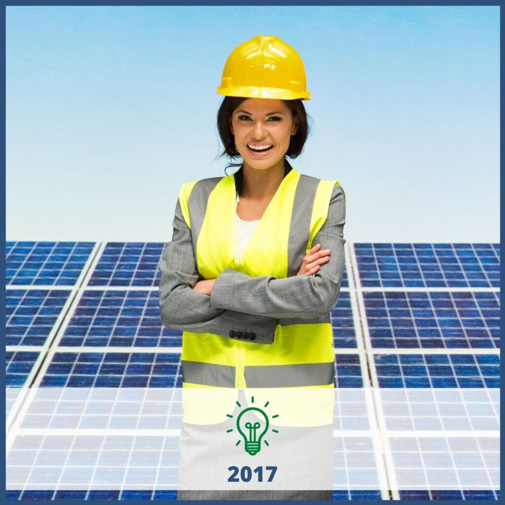 Female technician in front of solar panels