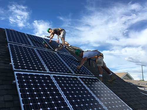 Two men installing three rows of solar panels on a roof