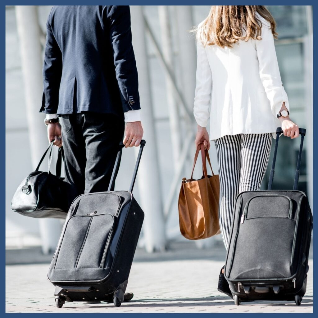 Business man and women walking and pulling suitcases