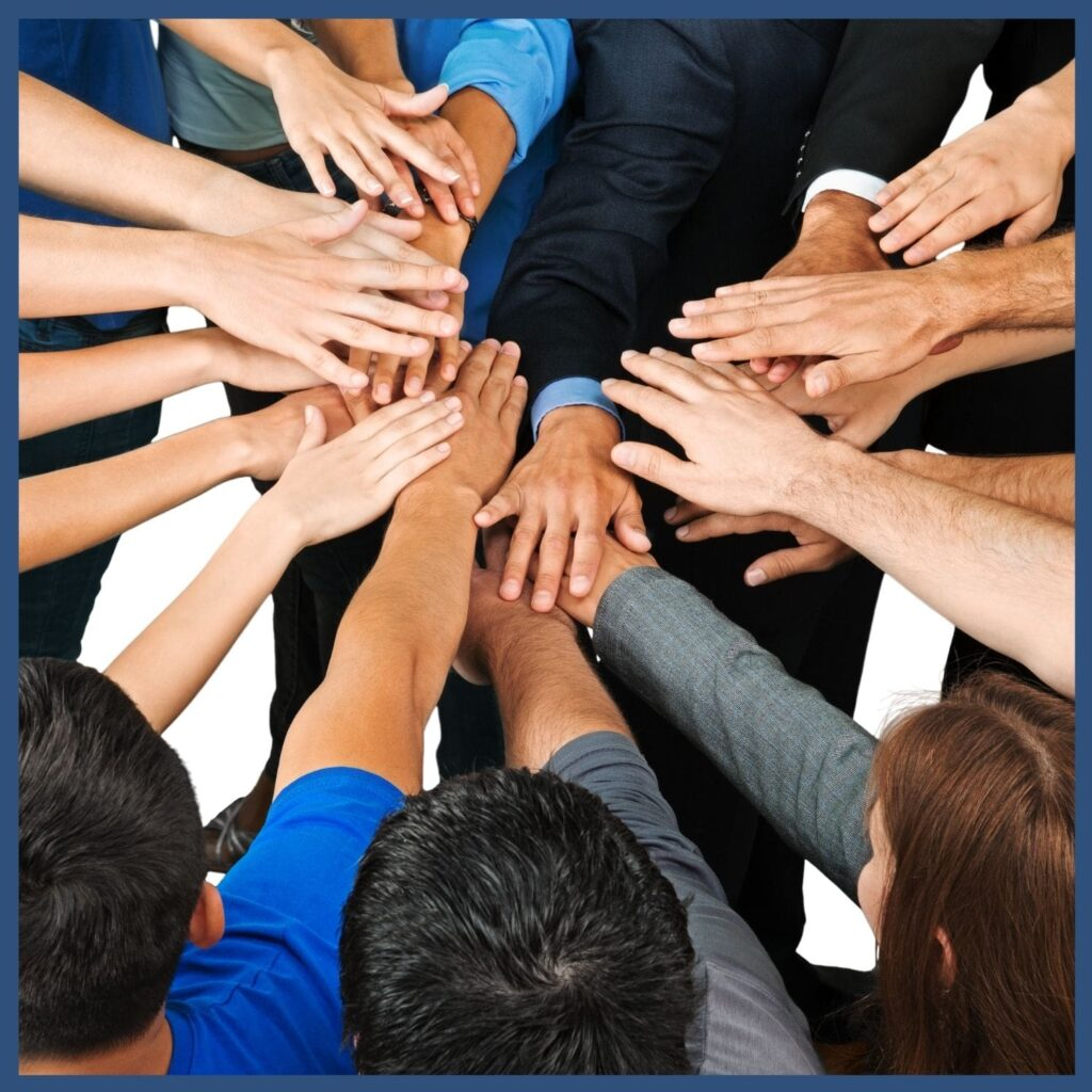 Business people in a circle with hands meeting in the middle