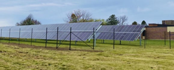 Rows of solar panels with building in background