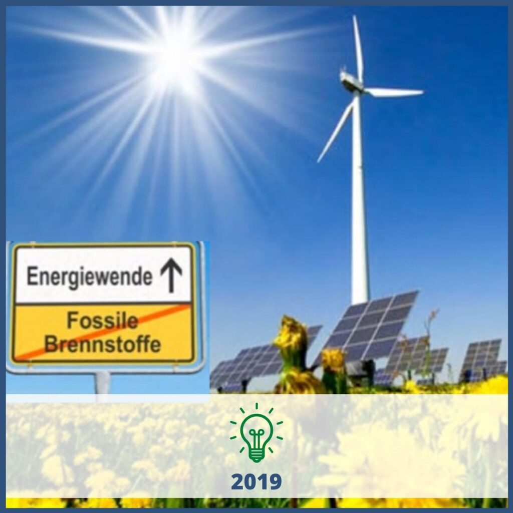 """Wind turbine, solar panels and sunflowers with a sign saying """"Energiewende"""""""