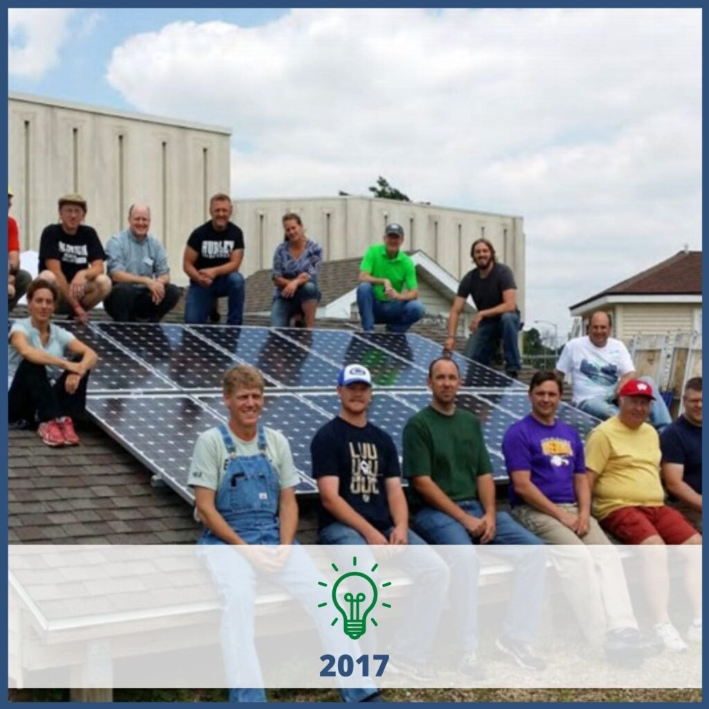 Students sitting on a demo roof with solar panels