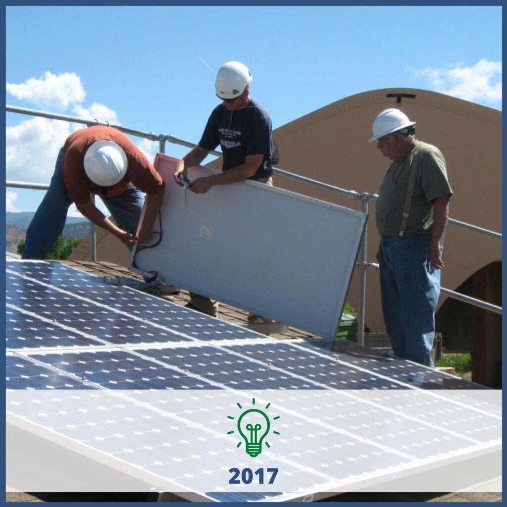 Three technicians installing solar panels