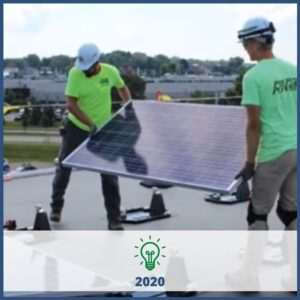 Two technicians carrying a solar panel on a roof - 2020