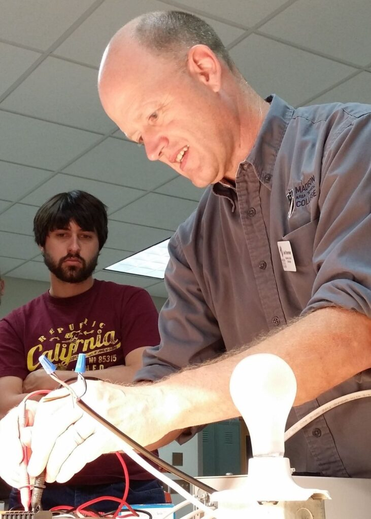 Joel Shoemaker conducting and experiment with a lightbulb