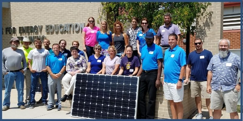 Workshop participants posing with a solar panel