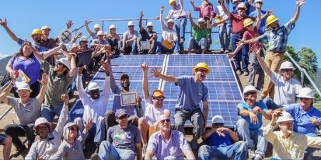 Team members from SEI around a solar panel