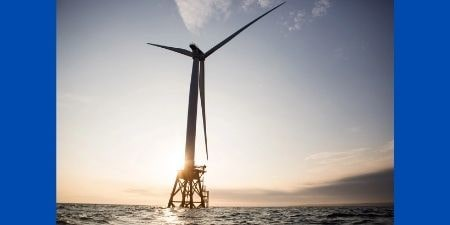 Wind turbine on ocean with blue background