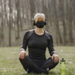 A Caucasian woman dressed in all black is vsitting in the meditative position with her legs crossed and eyes closed. Since it is during the pandemic of 2020-2021 she is wearing a facemask also black. she is sitting in an open field in the middle of the forest.