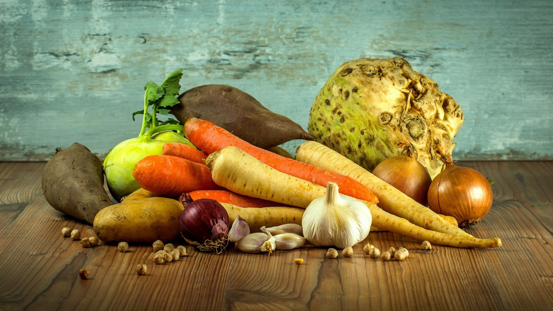 A pile of vegetables. Orange and yellow carrots, beets, onions, garlic, potatoes and nuts