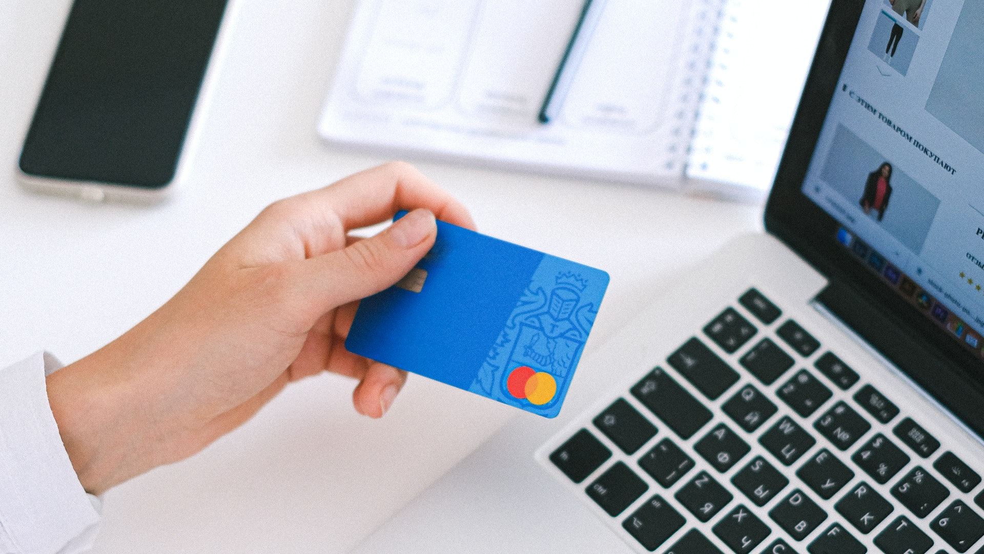 A woman is about to enter her Mastercard information in an online ecommerce POS. She is sitting at the computer holding her credit card in front of her.