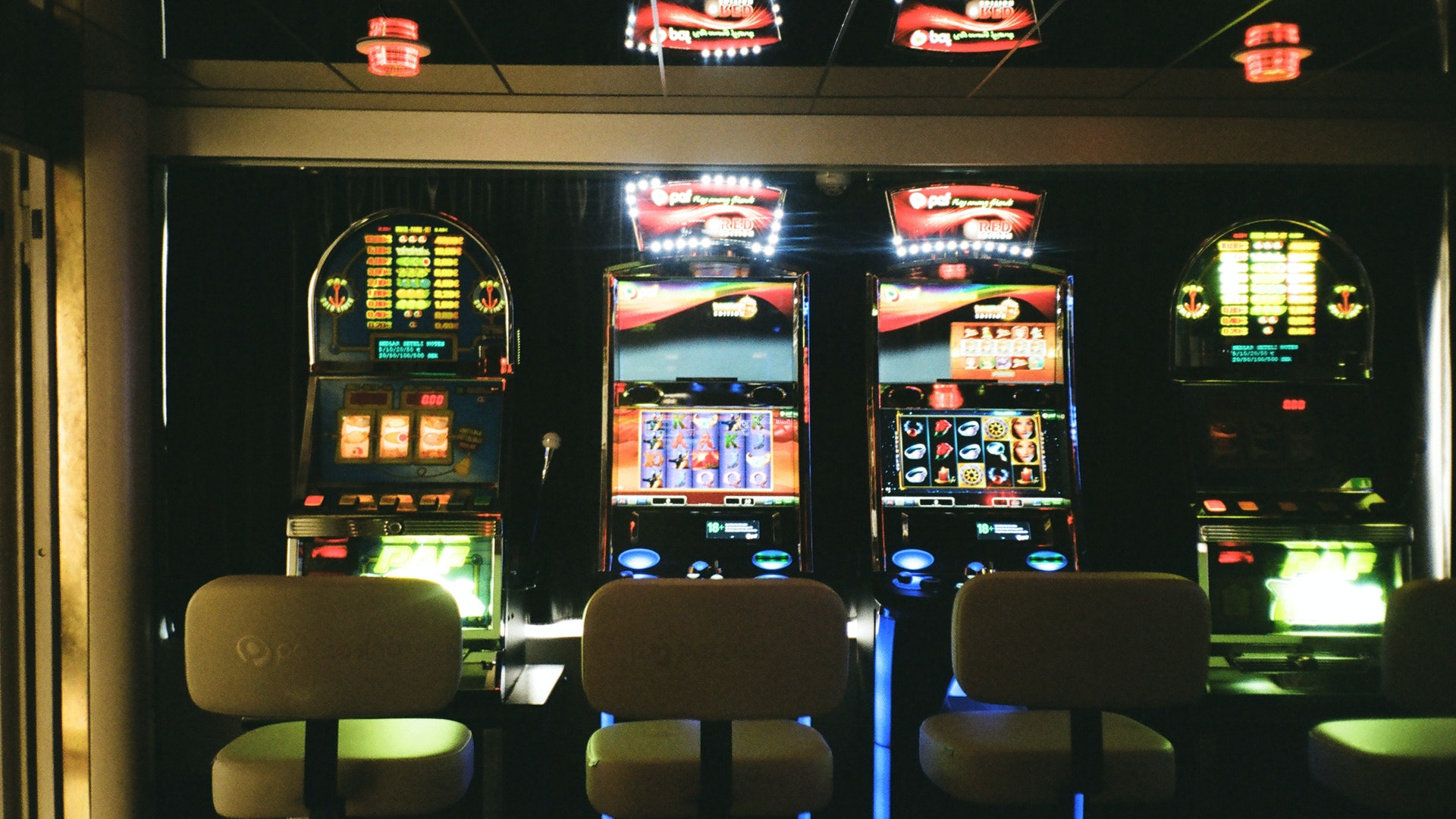 This image shows four adjacent slot machines to explain the gambling vertical. The seats in front of the machines are all empty.