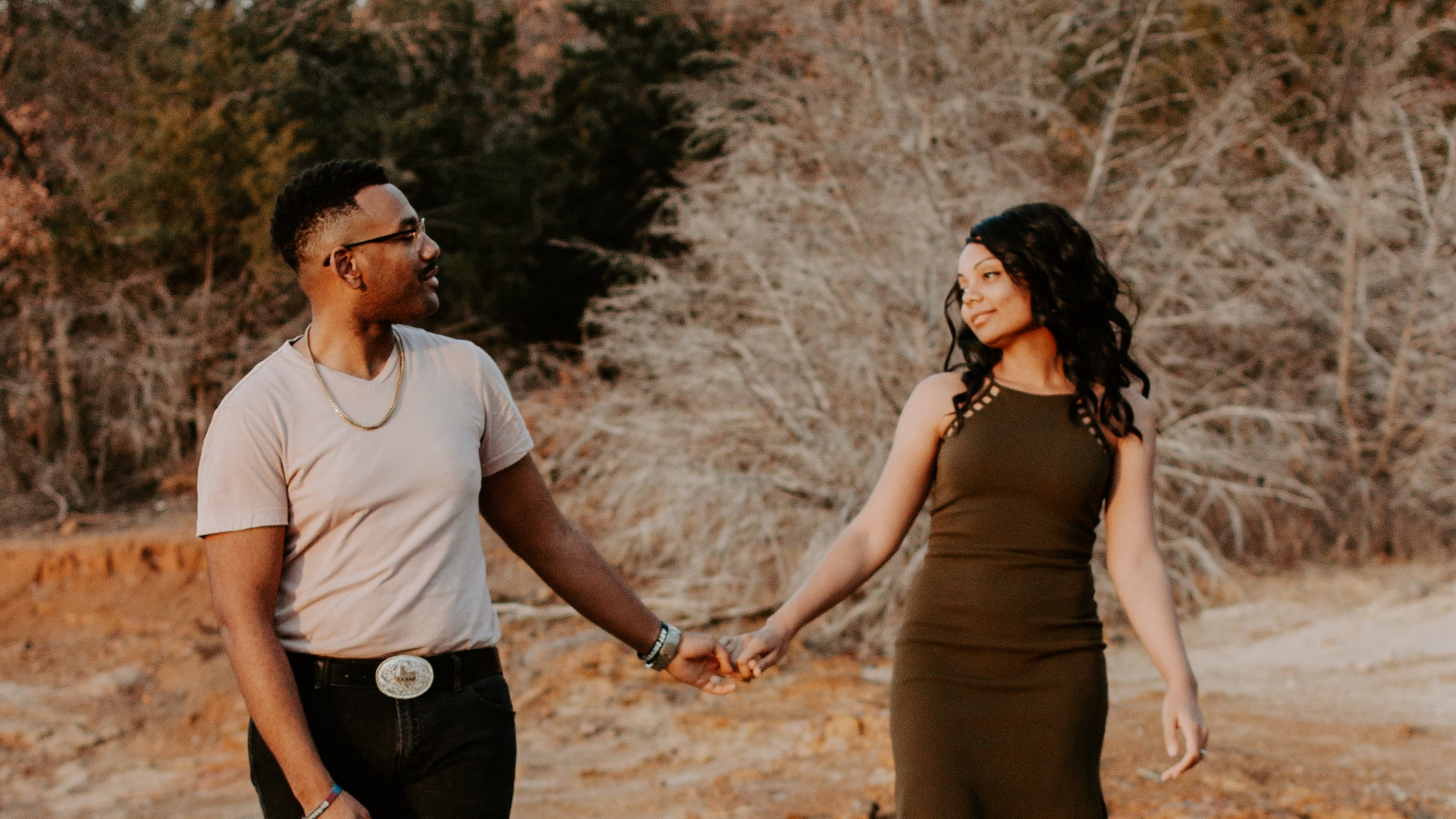 A black couple on a date holding hands walking a dusty trail in the peaceful woods during the daytime while gazing lovingly into each other's eyes.