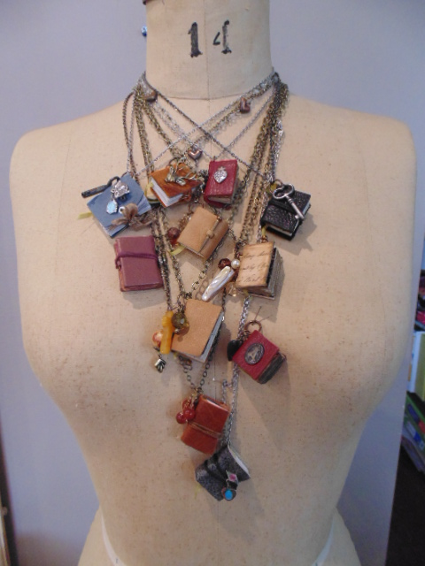 Mannequin with many mini book pendant necklaces