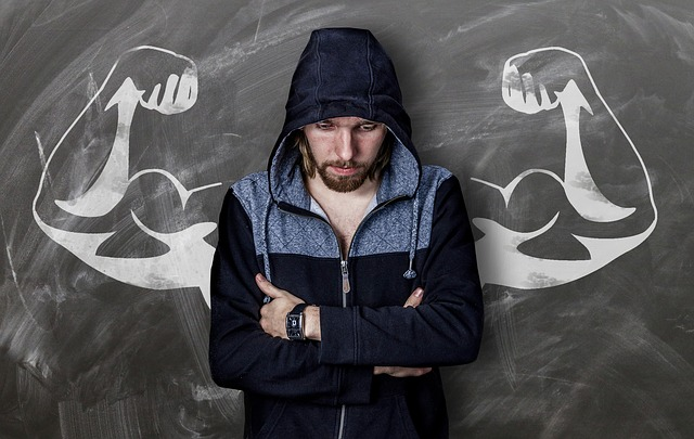 a man wearing a hoodie with arms crossed and staring down, stands in front of a blackboard where a chalk drawing of a mans muscled arms are behind