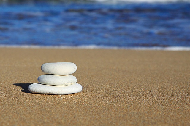 Three white beach pebbles balanced by graduated size on a brown sandy beach with a blue ocean in the background