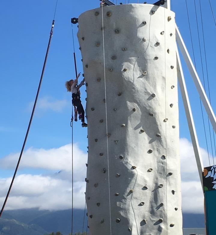 A woman rock climbing on an artificial boulder