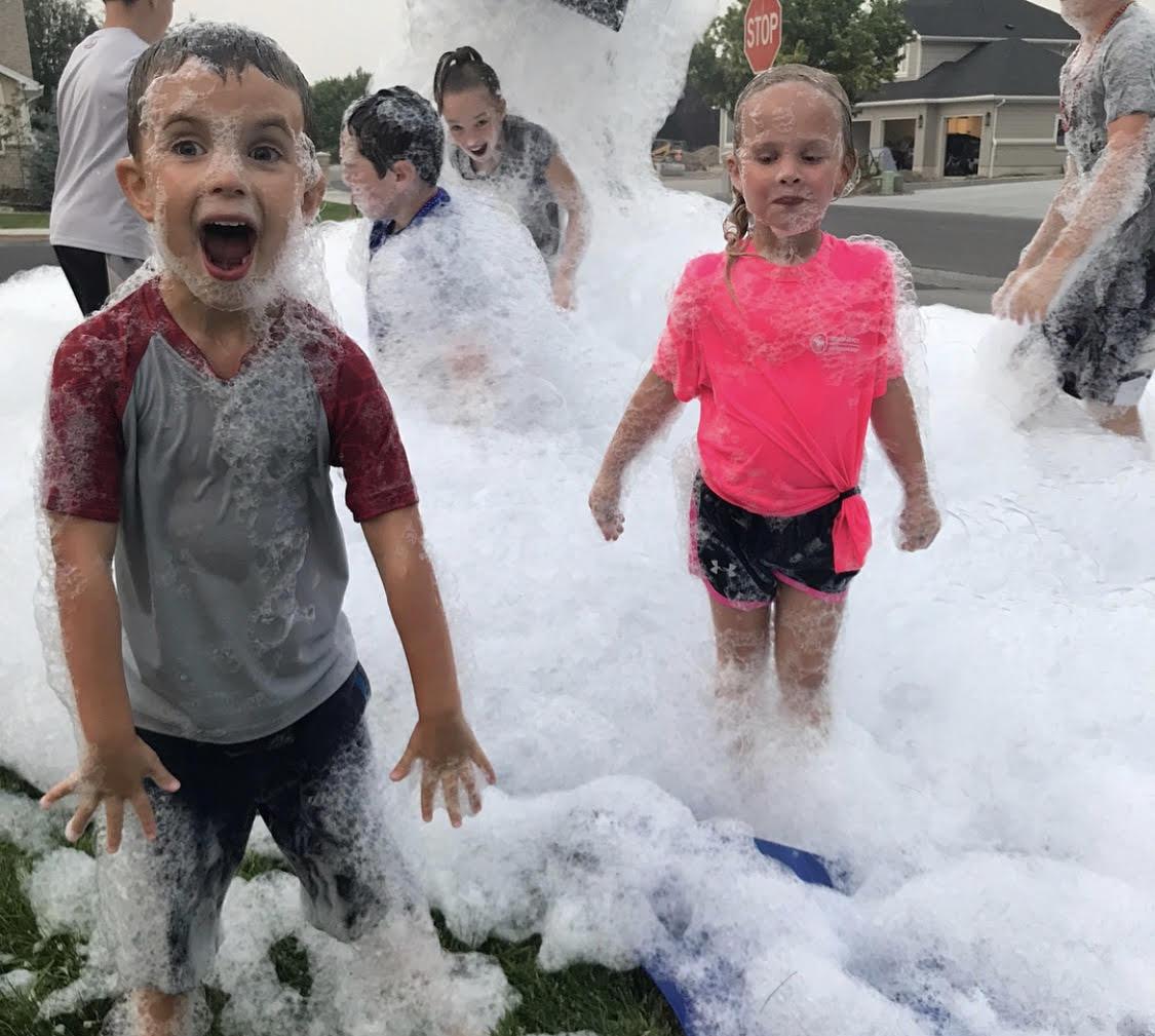 Children enjoying bubbles from a machine
