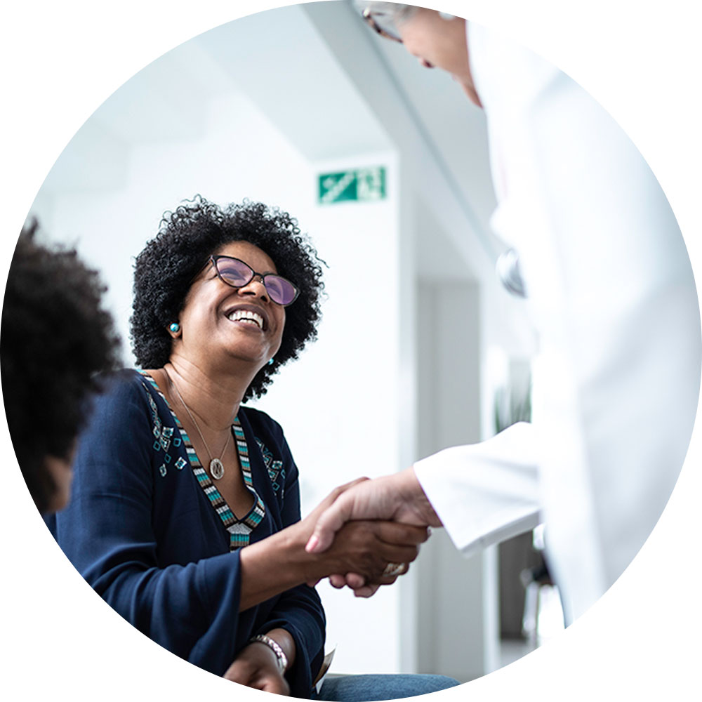Black woman smiling and shaking hands with doctor