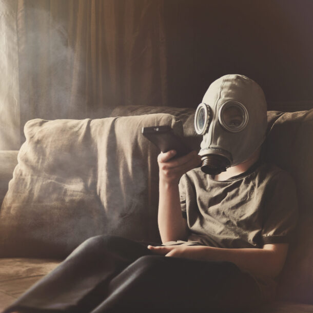 A young child is wearing a gas mask with a remote control watching televison on a couch with smoke and poulltion for a clean air concept.