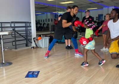 Photo of Boxing Trainer Zachary Thomas working with Shock-A-Bully student