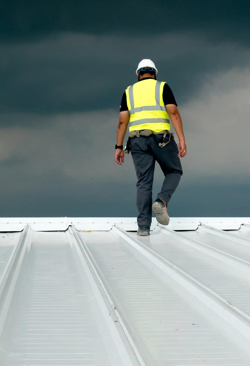 man standing on steel roof building