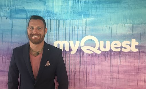 Rob Matzkin with blue jacket posing in front of wall with myQuest logo