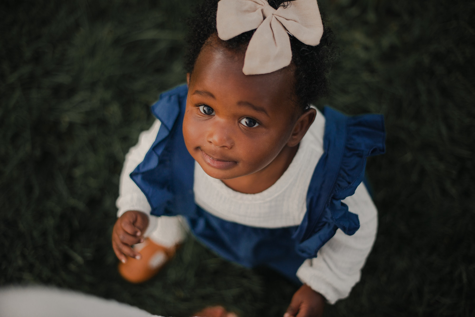 Beautiful black baby girl in old fashioned navy blue pinafore with sailor bow in the summertime