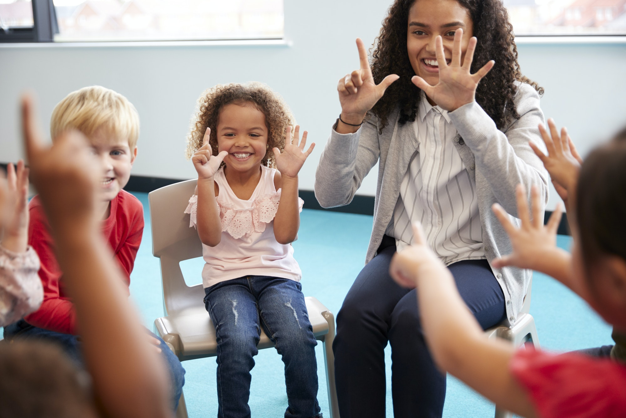 Front view of infant school children sitting on chairs in a circle in the classroom