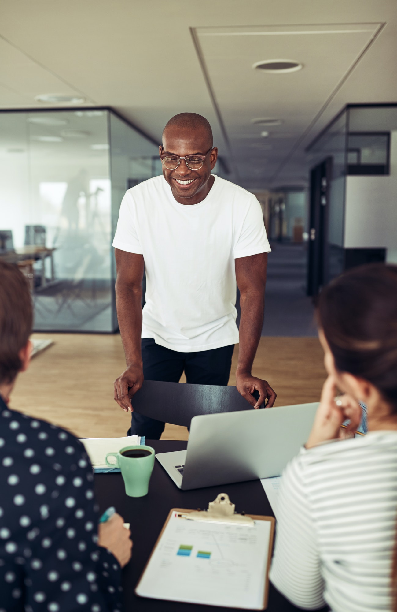 Smiling African businessman speaking with staff during an office meeting