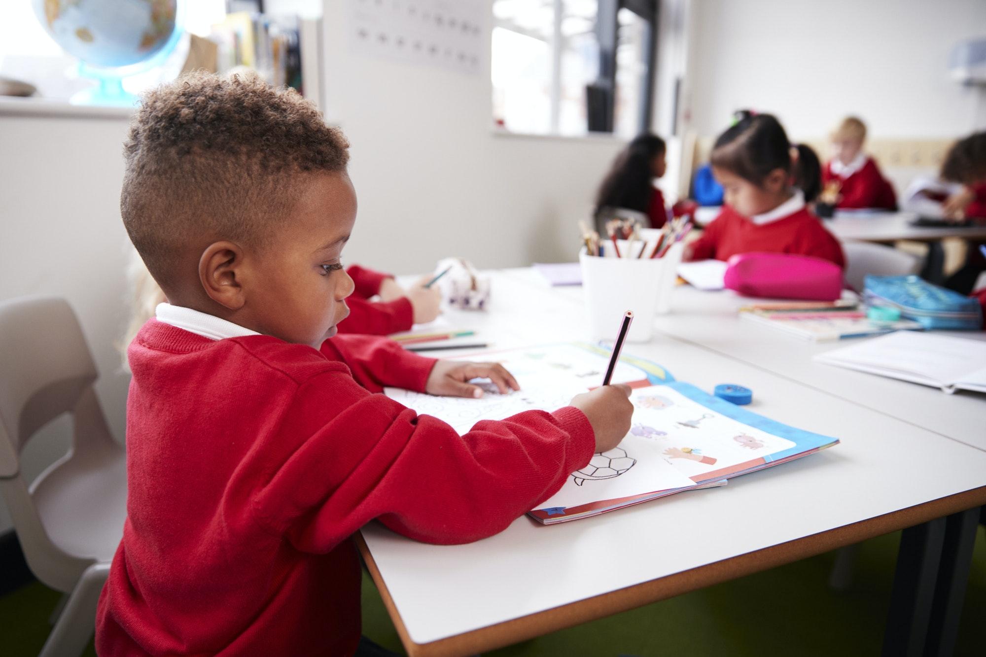Young black schoolboy wearing school uniform sitting at a desk in an infant school classroom drawing