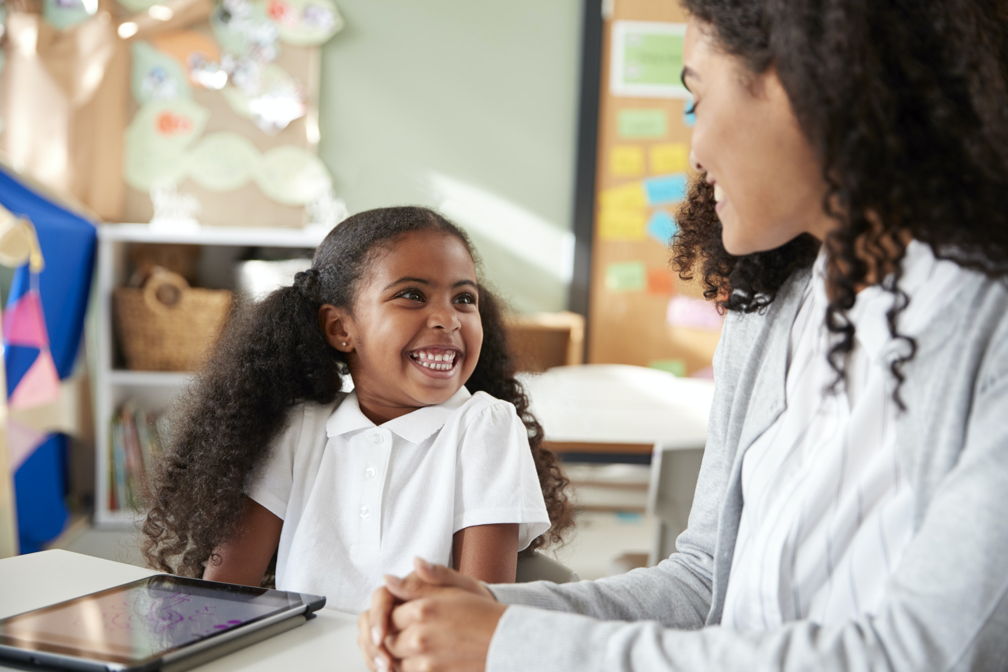 Young black schoolgir with a tablet computer in an infant school classroom, smiling