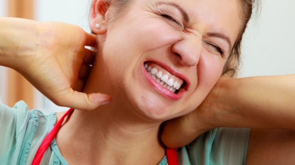 woman grabbing her neck in pain probably related to work injury